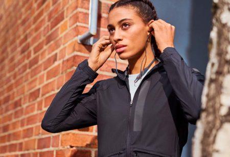 Une runner met des écouteurs pour faire du sport