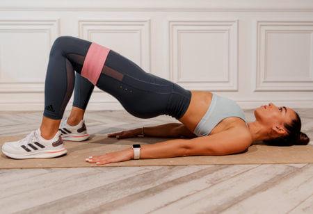 una donna allena gambe, glutei e addominali con la banda elastica