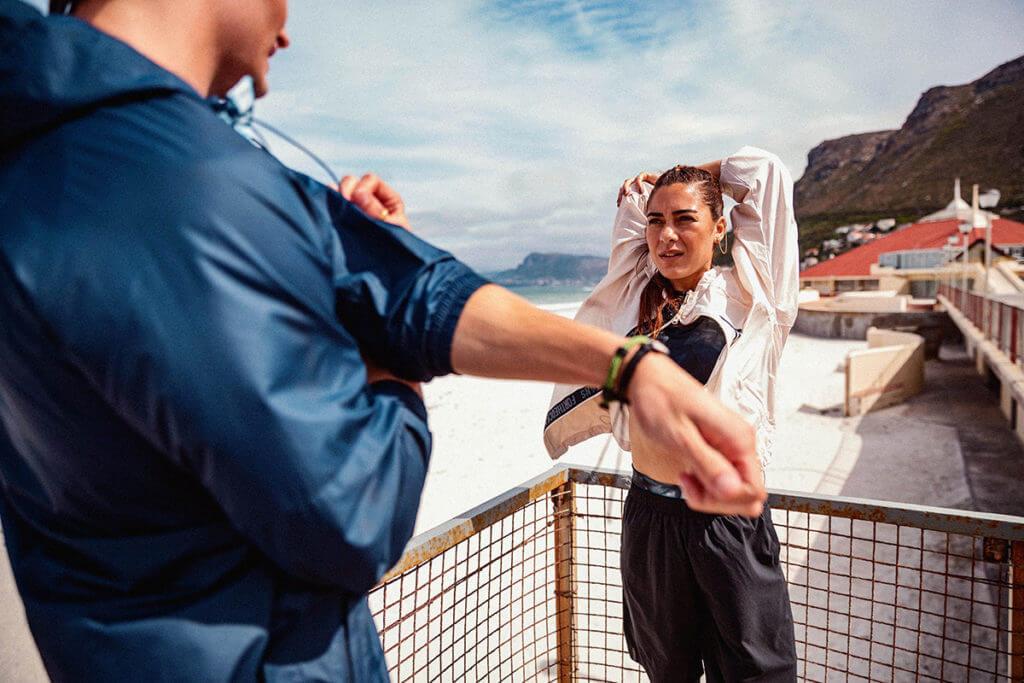 Atletas se alongando para treinar e garantir os benefícios da supercompensação