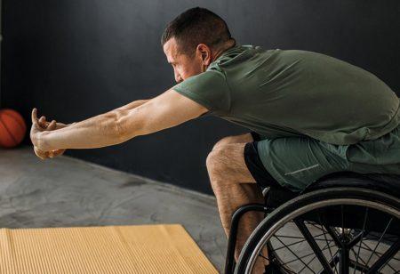 uomo in sedia a rotelle fa esercizi di stretching